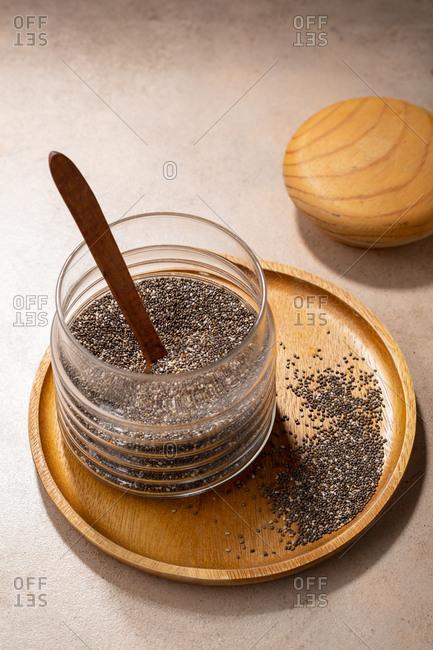 Chia seeds in storage jar on wooden plate