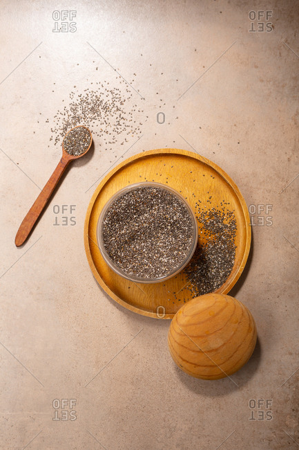 Overhead view of chia seeds in storage jar and scattered on light background