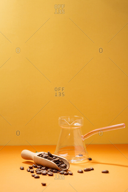 Coffee beans with wooden spoon and glass coffee pot