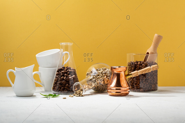Coffee pot and coffee cups on a white table with coffee beans