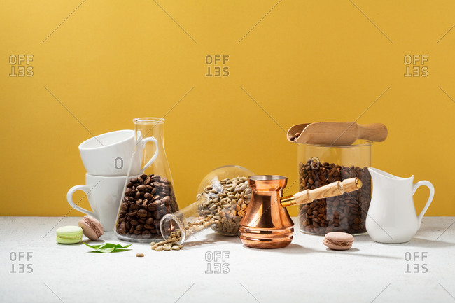 Coffee pot and coffee cups on a white table with coffee beans in front of yellow wall