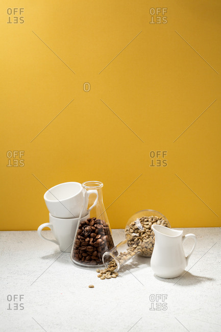 Coffee cups on a white table with brown and green coffee beans in glass flask