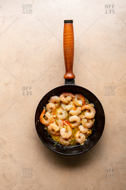 Sauteed garlic shrimp in pan on a light surface