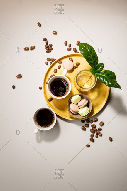 Overhead view of coffee in two white cups and macarons