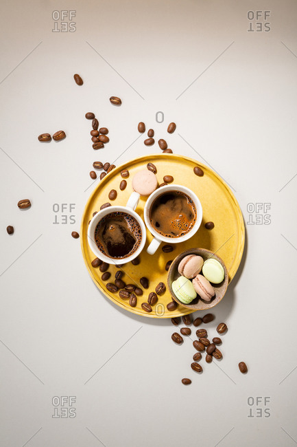 Overhead view of two cups coffee on tray with macaroons