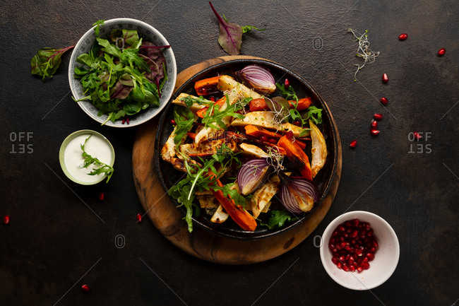 Overhead view of roasted vegetables on a dark surface