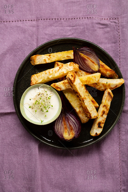 Overhead view of roasted celery wedges and aioli on dark plate