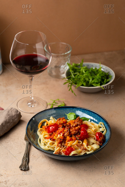 Pasta Bolognese and red wine on light table
