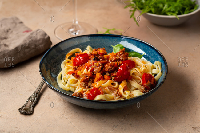 Pasta Bolognese in a blue bowl on a light table