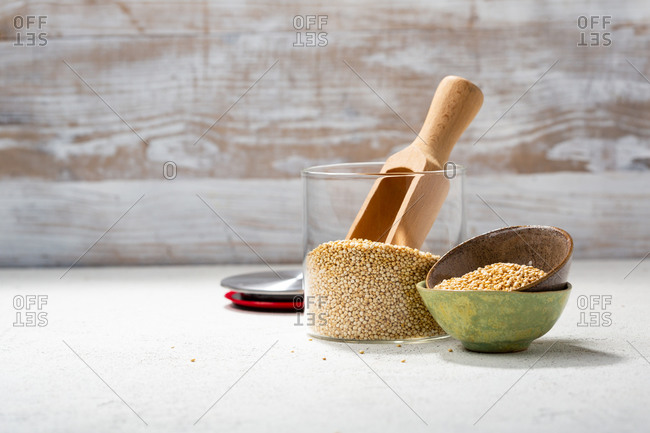 Quinoa in a glass jar and small bowls with a wooden scoop