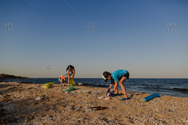Family picking up rubbish on polluted beach. Mother and two sons cleaning beach and putting garbage into plastic bin bags.