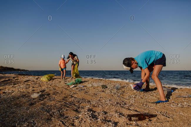Boy collecting litter on beach with his mother and brother. Two boys and woman picking up garbage found on the beach and putting it into plastic bin liners.