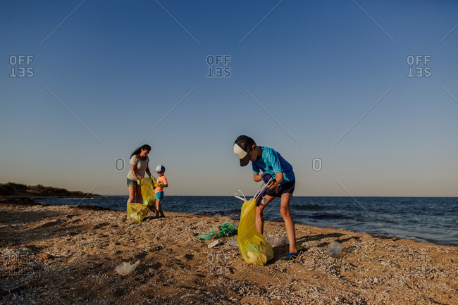 Two boys collecting rubbish on beach with their mother. Woman and two boys filling plastic bags with plastic bottles and rubbish found on the beach.