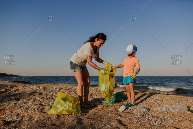 Mother collecting rubbish with son on beach. Woman and boy wearing rubber gloves filling plastic bag with rubbish left on the beach.