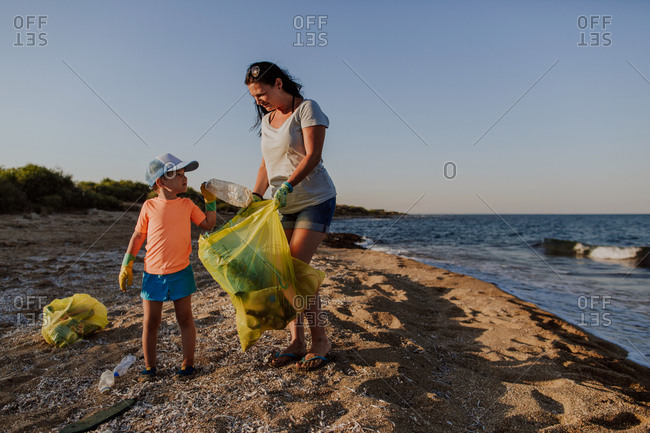 Young boy putting plastic bottle in bin liner. Mother and son filling garbage bag with rubbish and litter found on the beach.