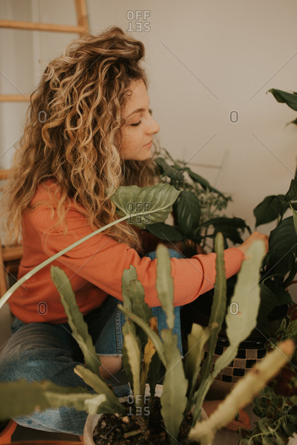 Blonde woman with curly hair tending to her indoor plants