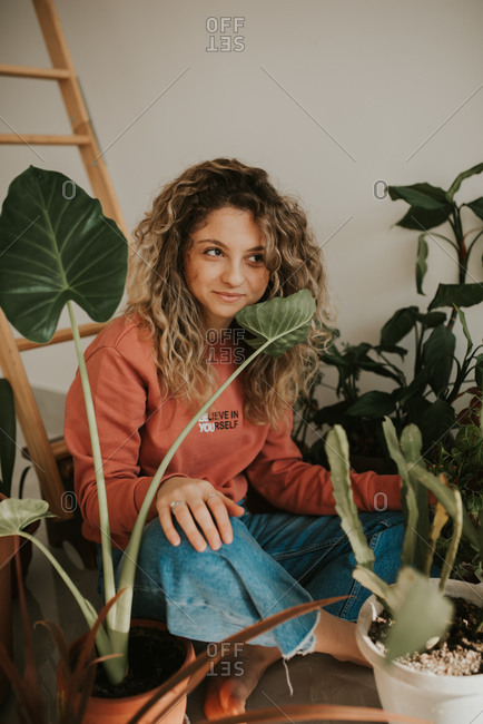 Woman with curly blonde hair tending to her house plants