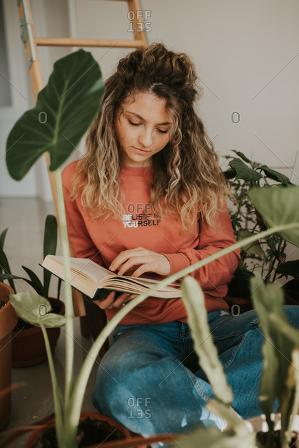 Woman with curly blonde hair reading a book surrounded by house plants