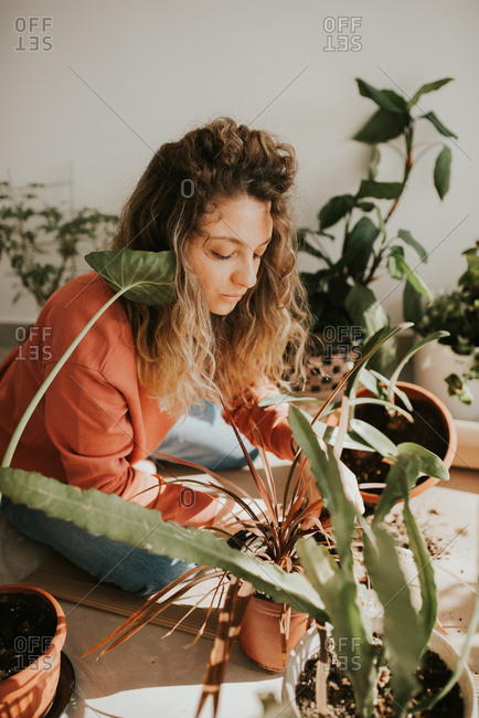 Woman with curly hair tending to her plants