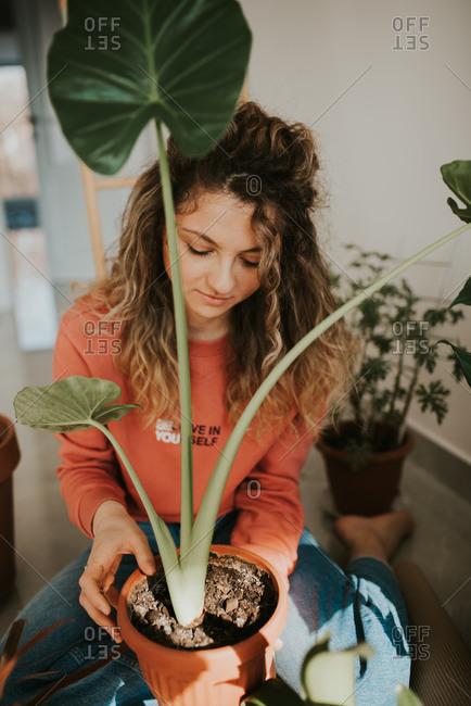 Young blonde woman with curly hair tending to her indoor plants