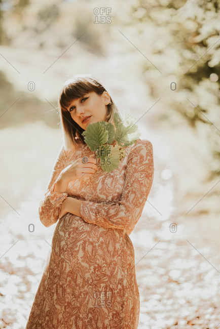 Pregnant woman standing outdoors holding leaves