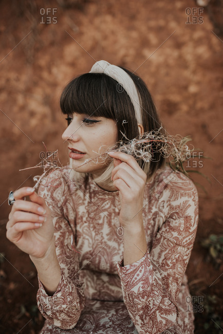 Beautiful woman holding branch by her face and looking away