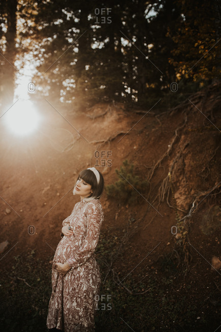 Pregnant woman standing in the woods holding her belly at sunset