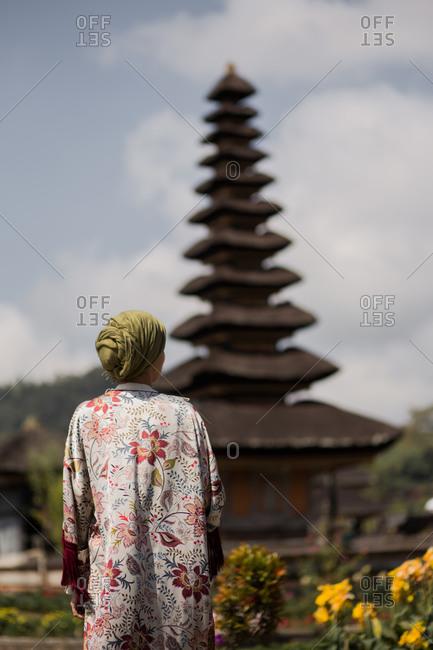 Back view of woman in front of Pura Ulun Danu Beratan Temple in Bali, Indonesia