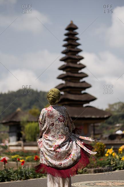 Woman dancing in front of Pura Ulun Danu Beratan Temple in Bali, Indonesia