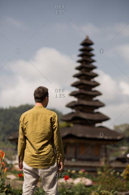 Back view of man standing in front of Pura Ulun Danu Beratan Temple in Bali, Indonesia