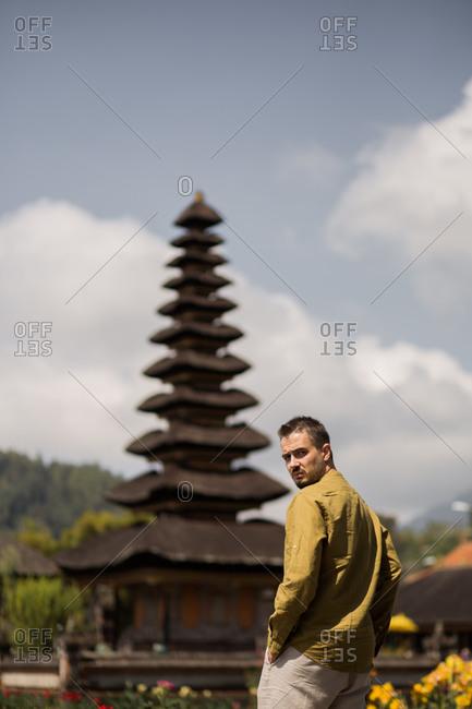 Man looking over his shoulder at the Pura Ulun Danu Beratan Temple in Bali, Indonesia