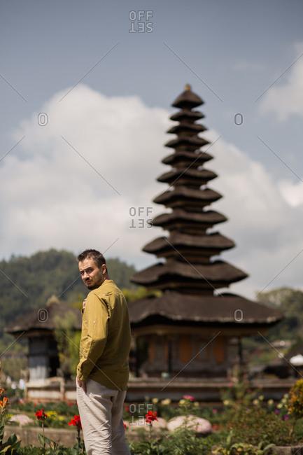 Man standing in front of Pura Ulun Danu Beratan Temple in Bali, Indonesia looking over his shoulder