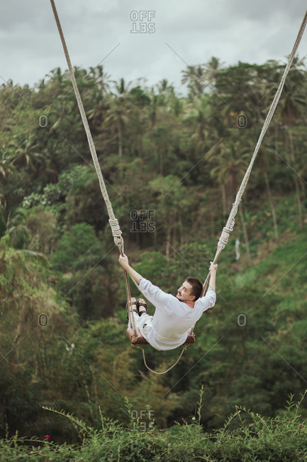Man swinging on rope swing above jungle in Bali, Indonesia