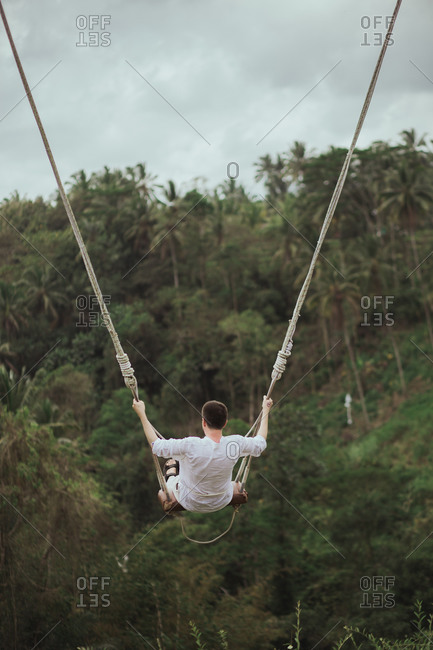 Rear view of man swinging on rope swing above jungle in Bali, Indonesia