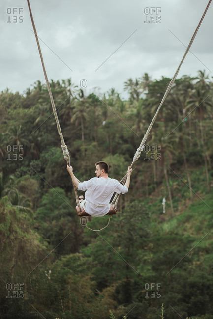 Young man swinging on rope swing above jungle in Bali, Indonesia