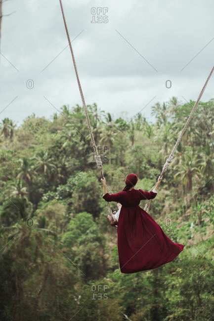 Woman swinging on rope swing above jungle in Bali, Indonesia