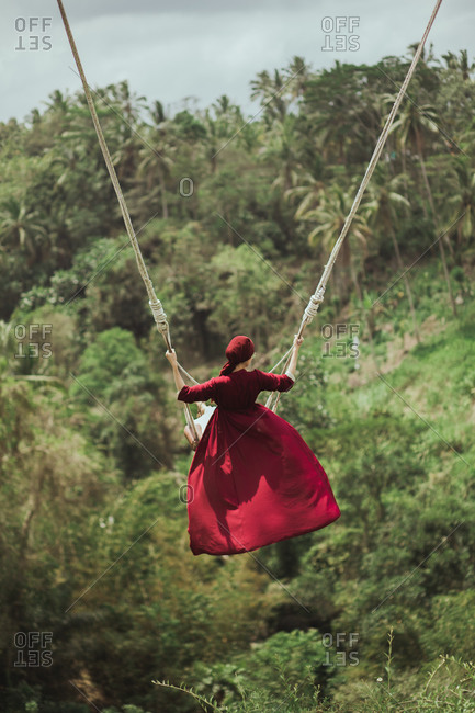 Woman in red dress swinging on rope swing above jungle in Bali, Indonesia