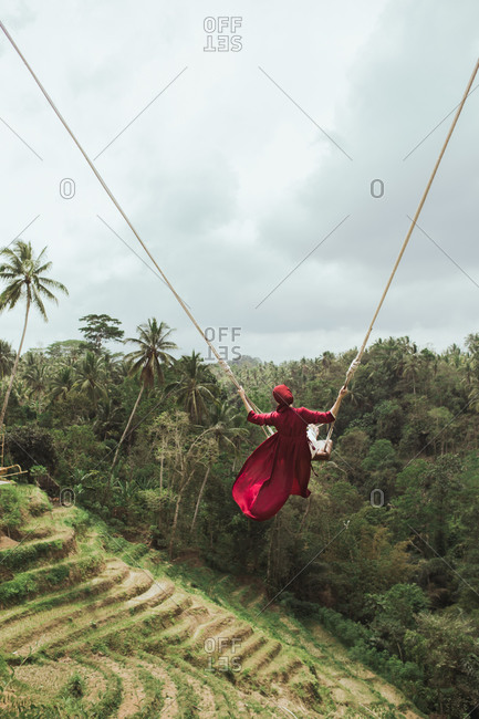 Woman swinging on rope swing over the jungle in Bali, Indonesia