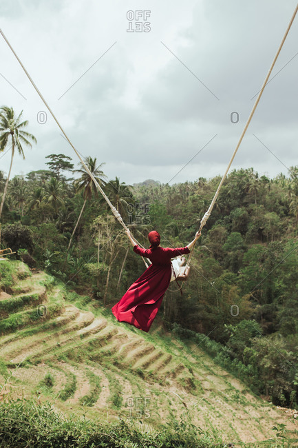 Rear view of woman swinging on rope swing above jungle in Bali, Indonesia