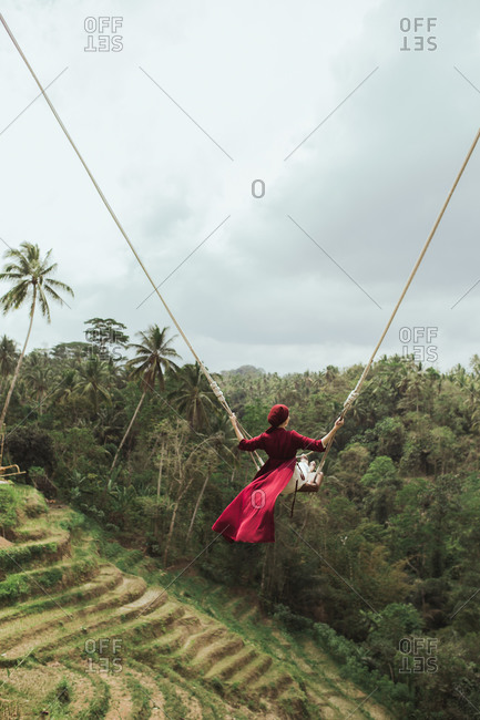 Back view of woman swinging on rope swing above jungle in Bali, Indonesia