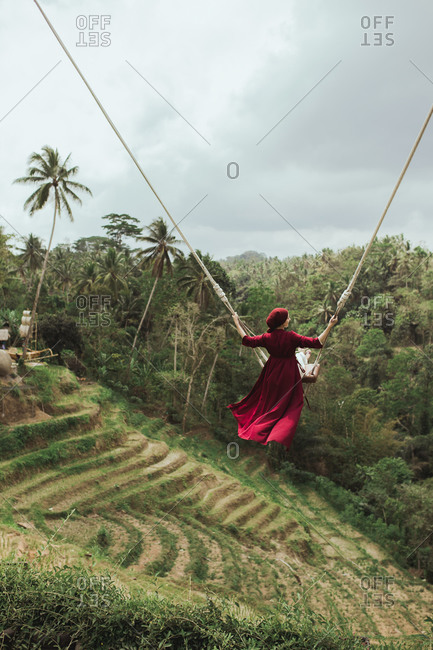 Rear view of woman in a red dress swinging on rope swing above jungle in Bali, Indonesia