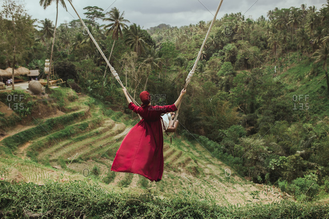 Woman wearing a red dress swinging on rope swing above jungle in Bali, Indonesia
