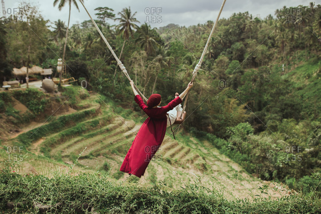 Carefree woman wearing a red dress swinging on rope swing above jungle in Bali, Indonesia