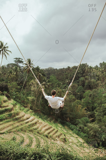 View of man swinging on rope swing above jungle in Bali, Indonesia from behind