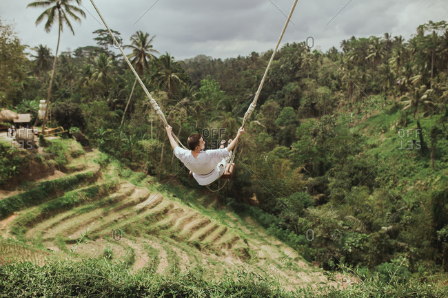 Man swinging on rope swing above jungle in Bali, Indonesia from behind