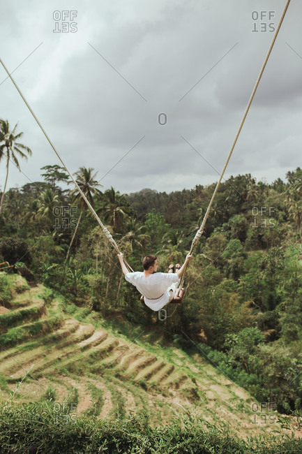 A man swinging on rope swing above jungle in Bali, Indonesia