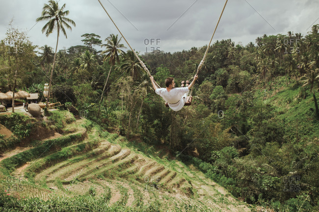 A man swinging on rope swing over palm trees in the jungle in Bali, Indonesia