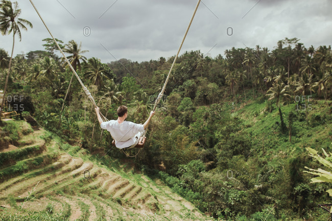 Man swinging on rope swing overlooking the jungle in Bali, Indonesia