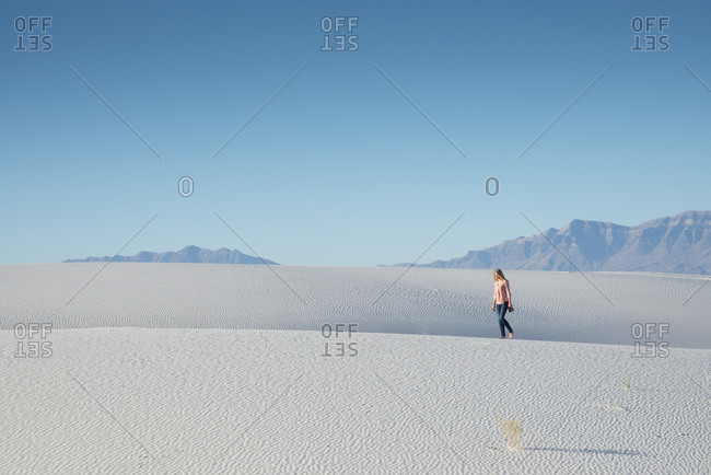 A woman walking along a sand dune in White Sands National Park near Alamogordo, New Mexico