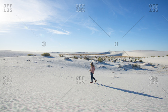 Woman walking along a sand dune in White Sands National Park near Alamogordo, New Mexico